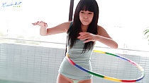 Machiko playing with a hula hoop wearing tight striped green vest long hair down over her breasts