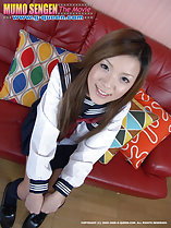 Japanese kogal Yua Ando sitting in uniform on couch hands on her knees