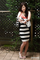 Standing in garden wearing striped dress pulling dress down exposing bra wearing high heels