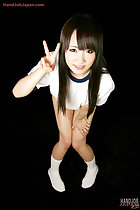 Leaning forward flashing victory sign hand resting on her thigh knees pressed together in white socks