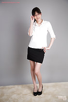 Office lady wearing white shirt in short black skirt wearing high heels adjusting her glasses