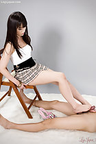 Sitting on wooden chair long hair over her white topmwearing plaid short skirt giving footjob with bare feet