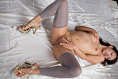 Lying Naked On Satin Sheet Wearing Grey Leggings In Gold High Heels Hand On Her Breast Hand Between Her Spread Legs On Her Shaved Pussy
