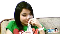 Sitting on couch fingering straw in soft drinks bottle wearing green tshirt