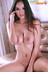 Mali Tai Seated On Couch Nude Pushing Back Her Long Hair Big Breasts Legs Open