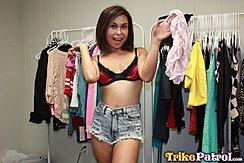 Standing Between Clothes Racks Wearing Bra In Denim Shorts Holding Top